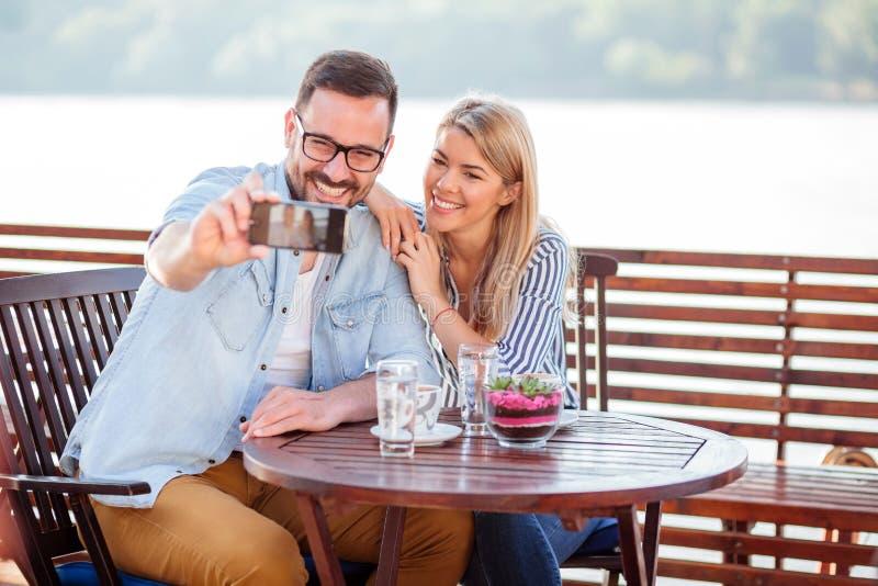 愉快的年轻在咖啡馆的夫妇饮用的咖啡,采取selfie 免版税库存图片