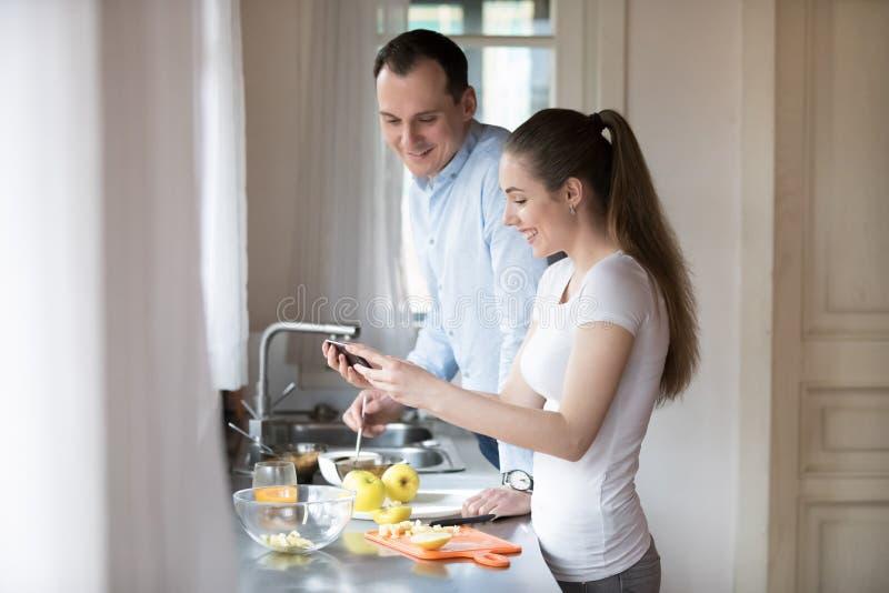 愉快的年轻在智能手机的夫妇观看的录影,当烹调时 免版税库存照片
