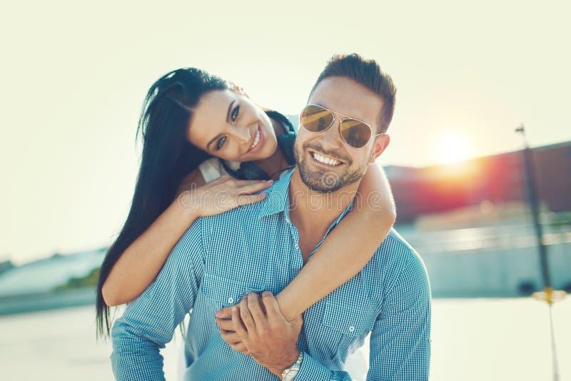 愉快的年轻在oudoors的夫妇微笑的肩扛姿势 库存图片