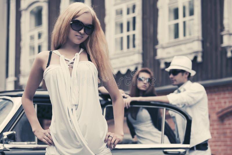 愉快的年轻太阳镜的时尚白肤金发的妇女在减速火箭的汽车旁边 库存图片