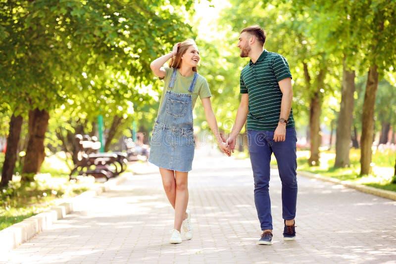 愉快的年轻夫妇在绿色公园在晴朗的春日 免版税库存图片
