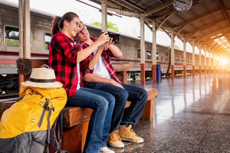 愉快的年轻夫妇旅行家一起在度假拍照片的在火车站,旅行概念,夫妇概念 免版税库存照片
