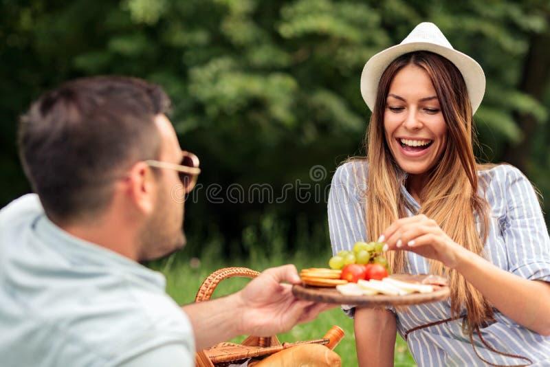 愉快的年轻夫妇有在野餐的了不起的时光在公园 库存照片