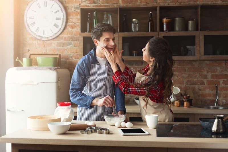 愉快的年轻夫妇烘烤在顶楼厨房里 库存图片