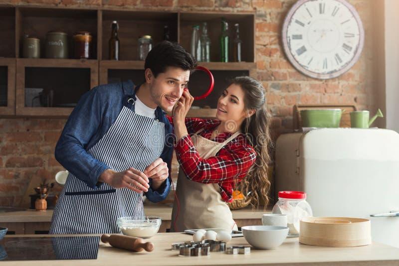 愉快的年轻夫妇烘烤在顶楼厨房里 免版税库存照片