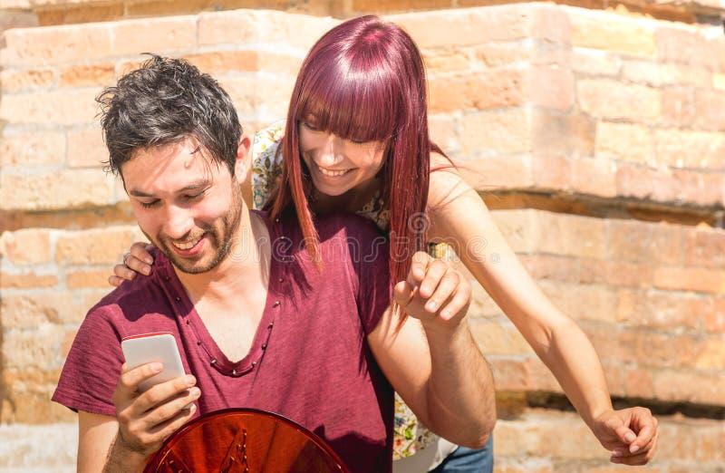 愉快的年轻夫妇获得与智能手机的乐趣在都市地点-友谊与行家最好的朋友的爱概念技术的 库存图片