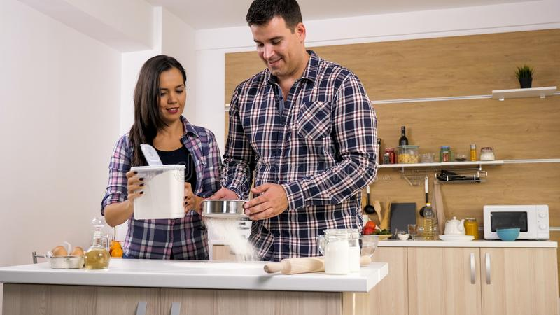愉快的年轻夫妇获得乐趣在室内现代厨房,当准备时 免版税图库摄影