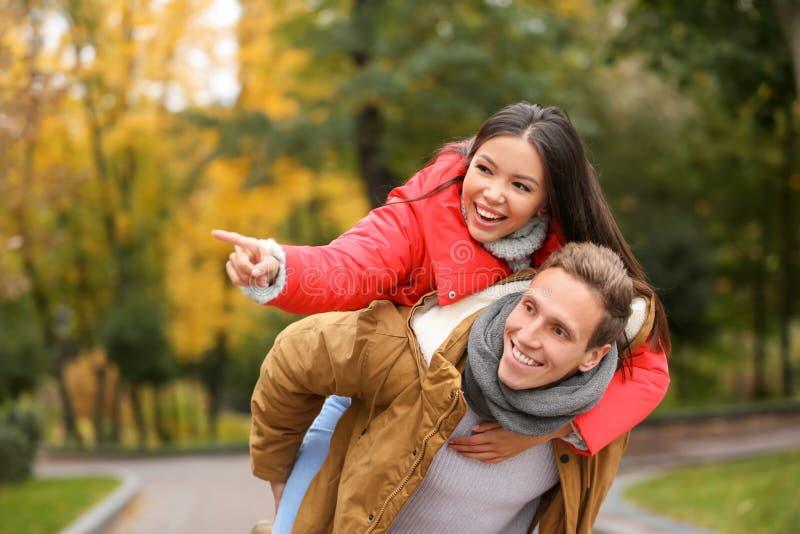 愉快的年轻夫妇获得乐趣在秋天公园 免版税图库摄影