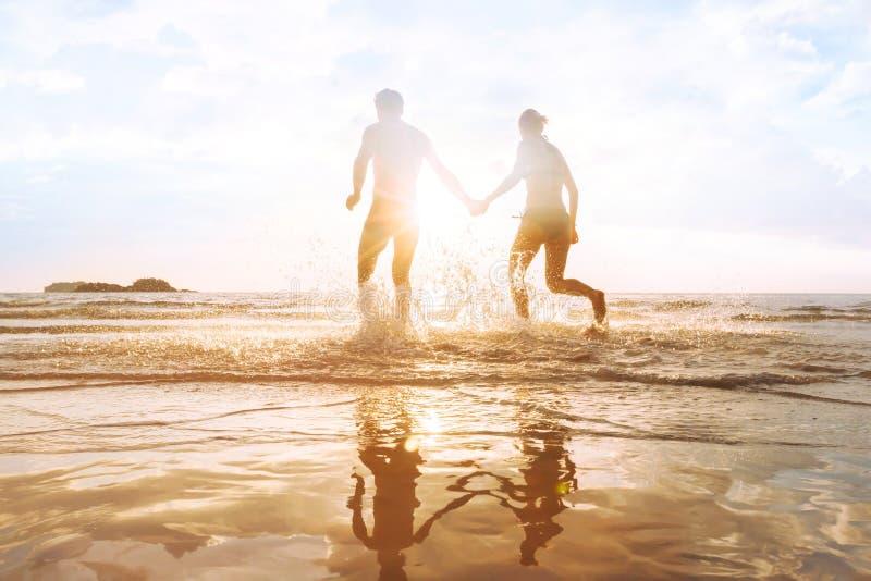 愉快的年轻夫妇获得在海滩在日落,水飞溅的乐趣 免版税库存照片