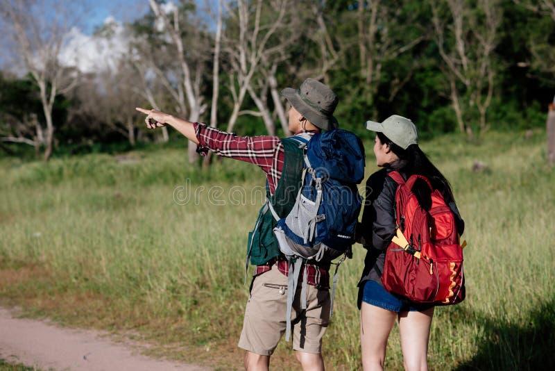 愉快的年轻夫妇走的暴涨在野营的帐篷衣服的森林里 库存照片