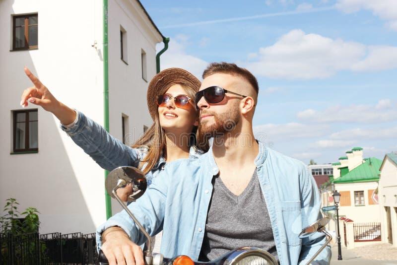 愉快的年轻夫妇骑马滑行车在镇里 英俊的人和少妇旅行 冒险和假期概念 免版税库存照片