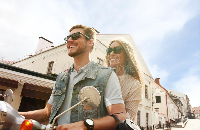 愉快的年轻夫妇骑马滑行车在镇里 英俊的人和少妇旅行 冒险和假期概念 库存图片