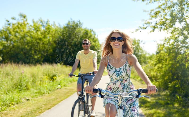 愉快的年轻夫妇骑马自行车在夏天 免版税库存照片