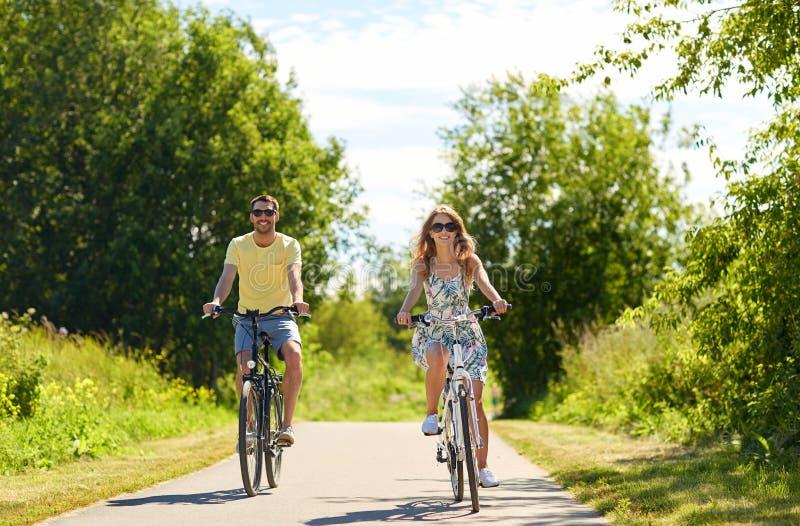 愉快的年轻夫妇骑马自行车在夏天 图库摄影
