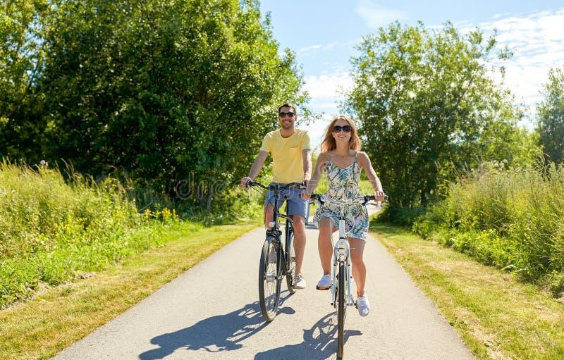 愉快的年轻夫妇骑马自行车在夏天 库存照片
