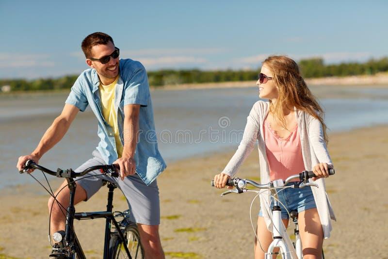 愉快的年轻夫妇骑马自行车在海边 免版税库存图片