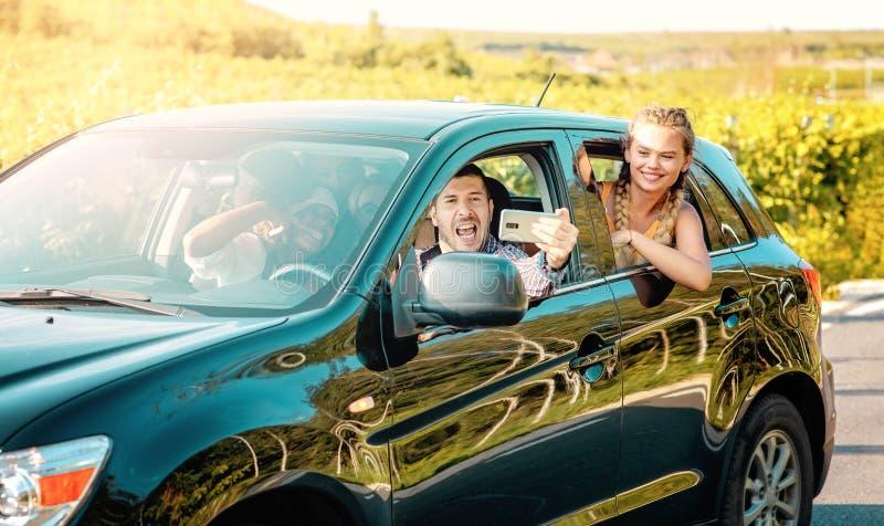 愉快的年轻女人和一起享受一个夏天的旅行的人司机 旅行住处 免版税图库摄影