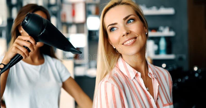 愉快的年轻女人和美发师有做热称呼的爱好者的 库存图片