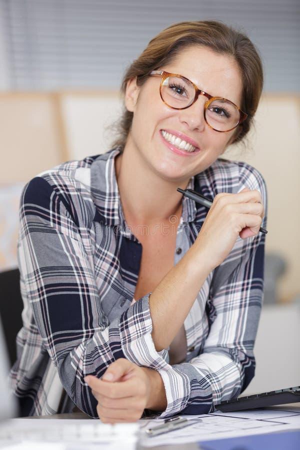 愉快的年轻女人在打电话的办公室 免版税库存照片
