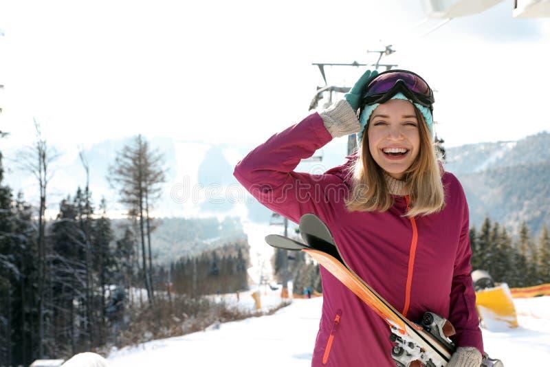 愉快的年轻女人用在驾空滑车附近的滑雪设备在山区度假村,文本的空间 免版税库存照片