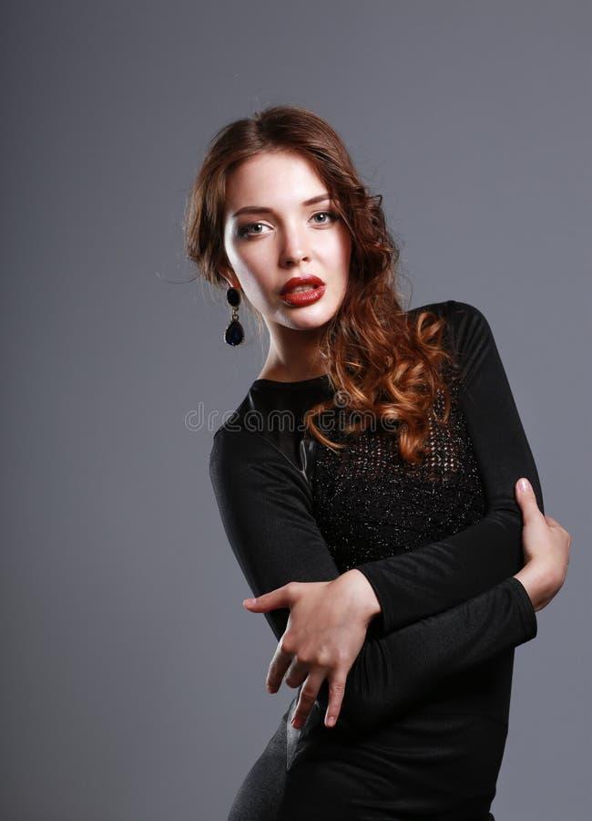 愉快的年轻女人画象黑礼服的在灰色背景 图库摄影