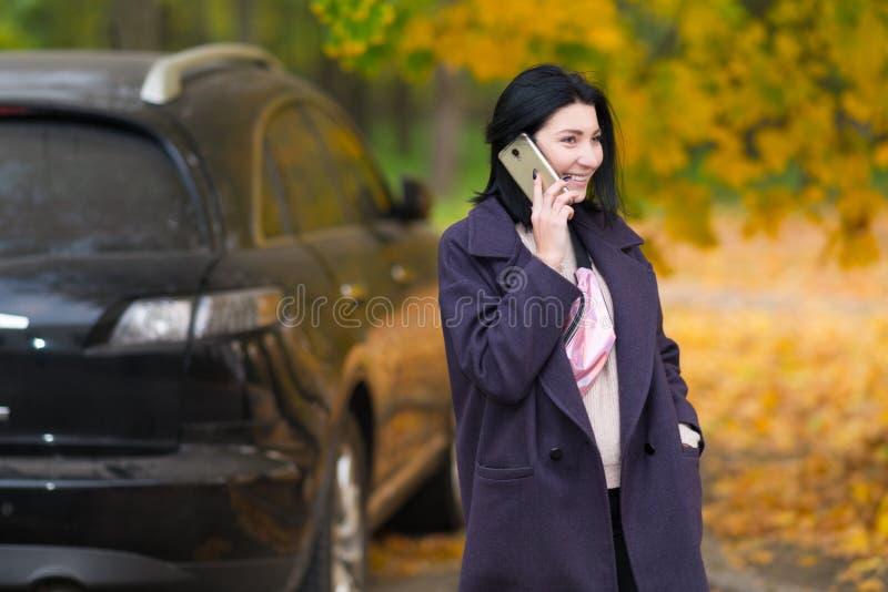 愉快的年轻女人谈话在她的流动户外 免版税库存图片