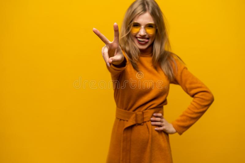 愉快的年轻女人身分的图象被隔绝在显示和平姿态的黄色背景 看照相机 图库摄影