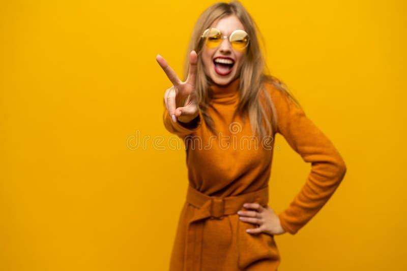 愉快的年轻女人身分的图象被隔绝在显示和平姿态的黄色背景 看照相机 库存图片