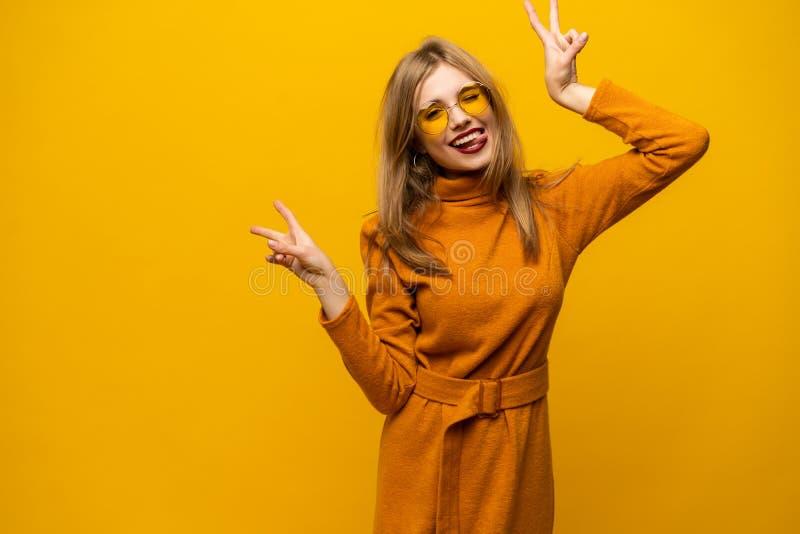 愉快的年轻女人身分的图象被隔绝在显示和平姿态的黄色背景 看照相机 免版税库存照片