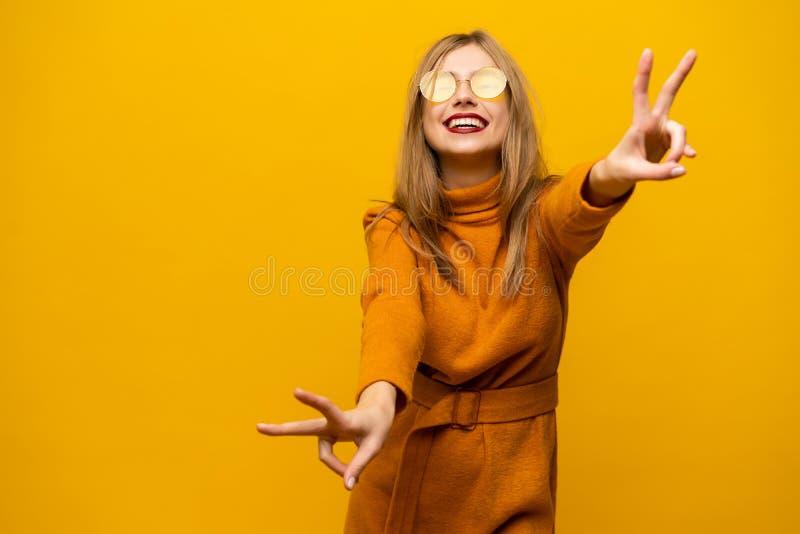 愉快的年轻女人身分的图象被隔绝在显示和平姿态的黄色背景 看照相机 免版税库存图片