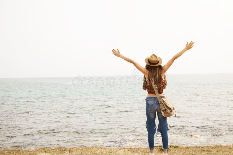 愉快的年轻女人身分胳膊举了被伸出的手并且海上享有在海滩的生活 免版税库存照片