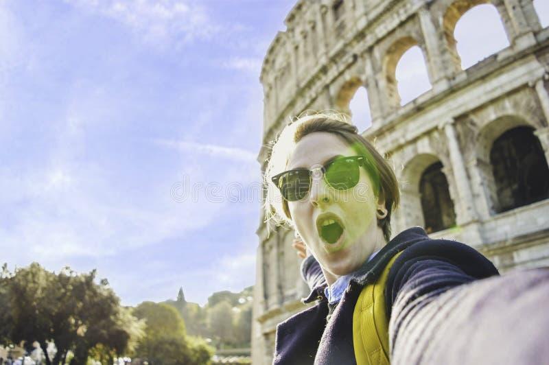 愉快的年轻女人采取在著名地标前面的selfie大剧场,罗马,意大利的旅行的欧洲 库存照片