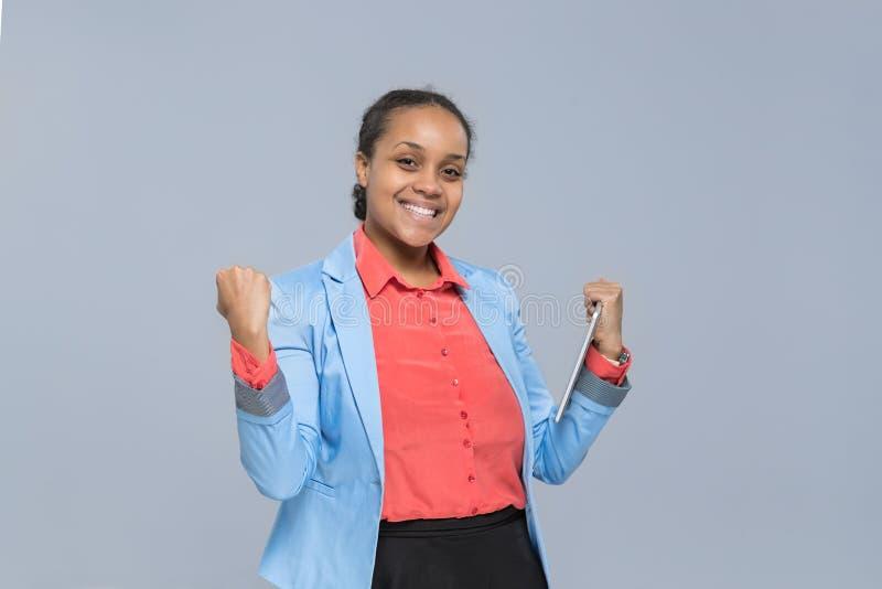 愉快的年轻女商人举行片剂计算机激动的非裔美国人的女孩 免版税库存图片