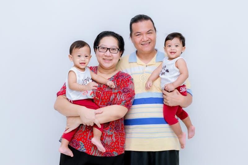 愉快的年轻家庭演播室画象有小孩的 在家拥抱双小女儿的父母在托儿所 免版税库存照片