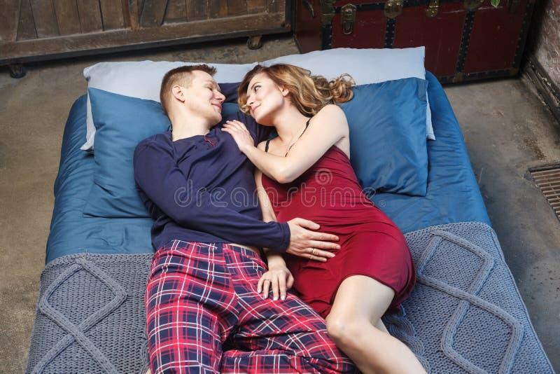 愉快的年轻家庭画象有休息在卧室,说谎在与互相看蓝色编织的格子花呢披肩的床上的睡衣裤的 免版税库存照片