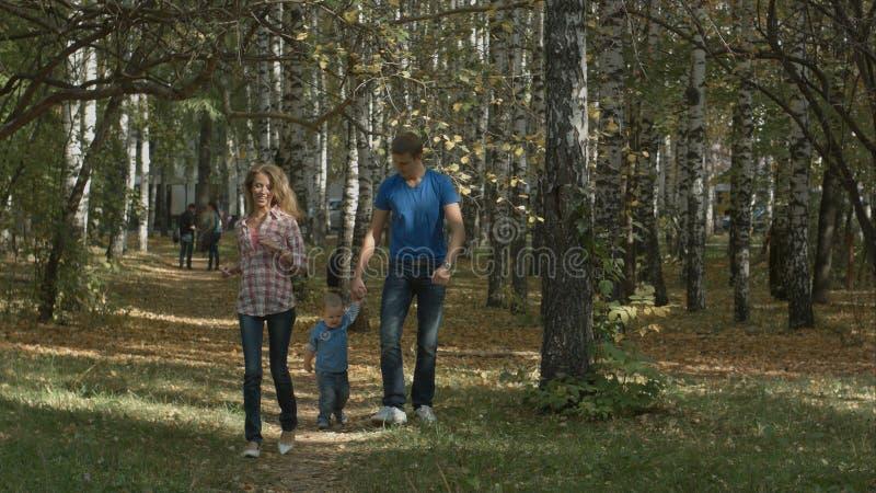 愉快的年轻家庭获得乐趣户外 母亲、父亲和他们的小男孩在公园跑 免版税库存图片