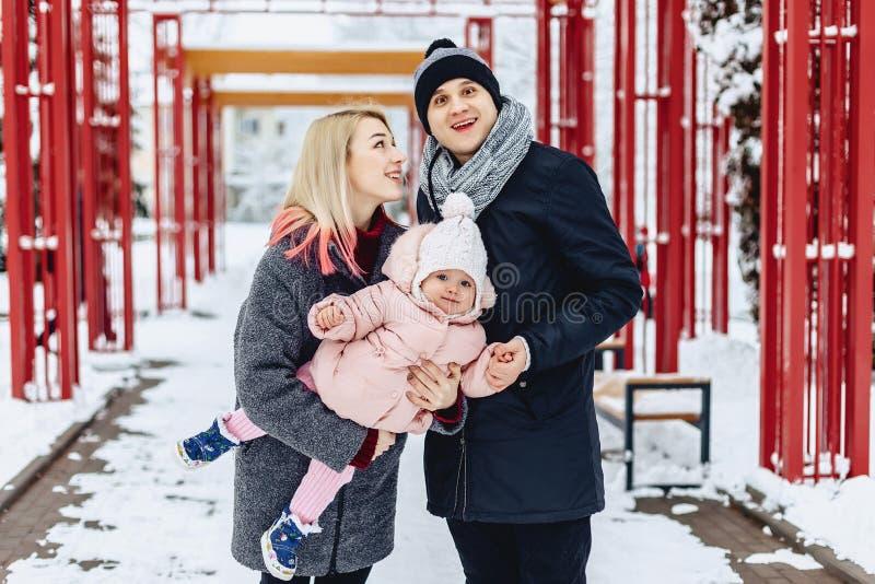 愉快的年轻家庭走与在冬天街道,妈妈,爸爸,c上的婴孩 免版税库存照片