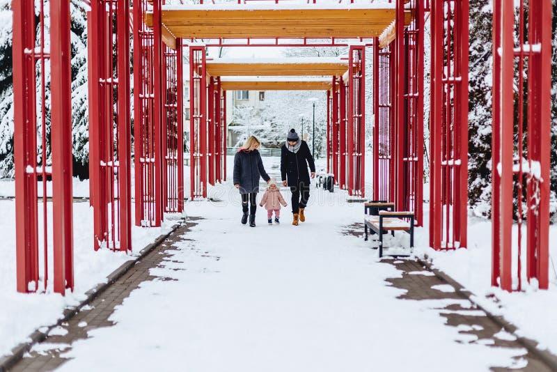 愉快的年轻家庭走与在冬天街道,妈妈,爸爸,c上的婴孩 库存照片