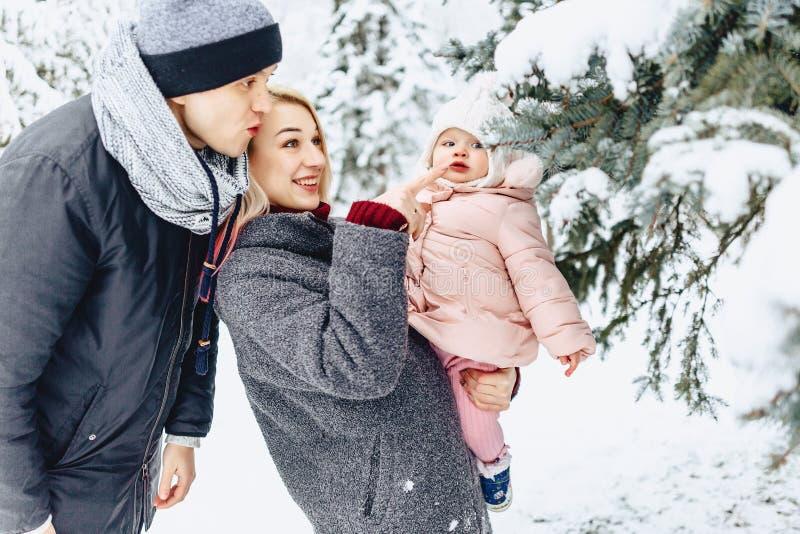 愉快的年轻家庭走与在冬天街道,妈妈,爸爸,c上的婴孩 图库摄影