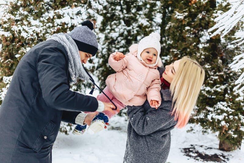 愉快的年轻家庭走与在冬天街道,妈妈,爸爸,c上的婴孩 库存图片