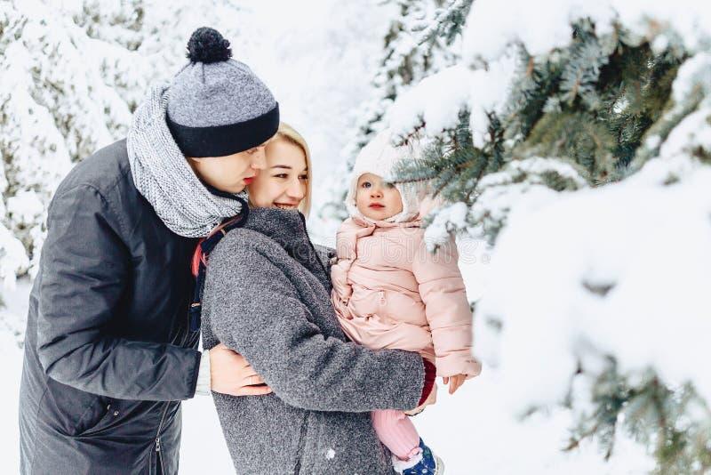 愉快的年轻家庭走与在冬天街道,妈妈,爸爸,c上的婴孩 免版税库存图片