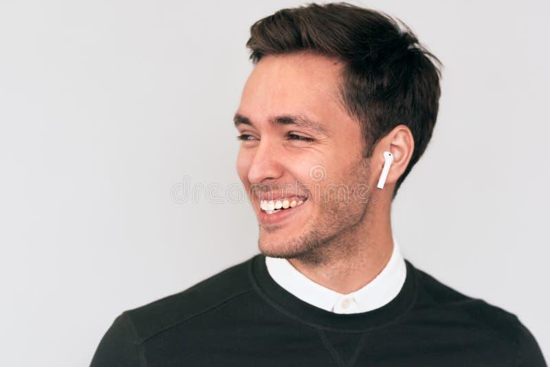 愉快的年轻帅哥讲话与朋友对喜讯说使用earbuds 免版税库存图片