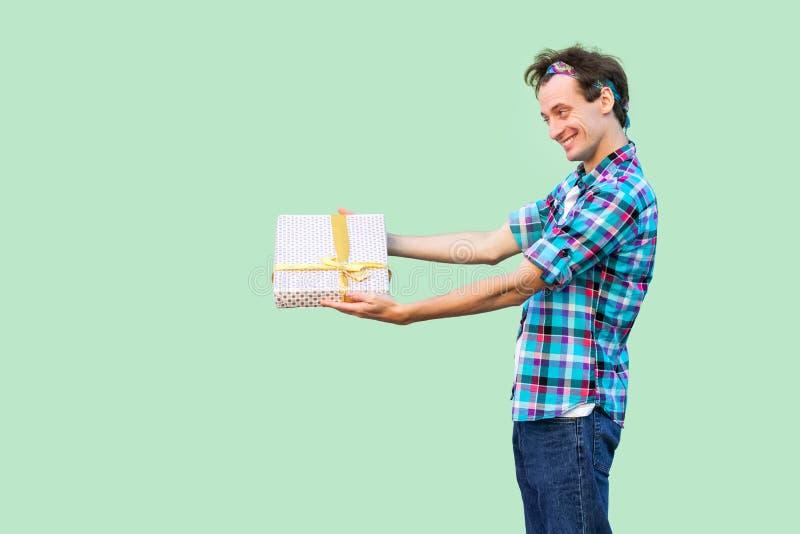 愉快的年轻成人行家人侧视图白色T恤和方格的衬衣身分的,给您当前与黄色弓, 免版税库存照片