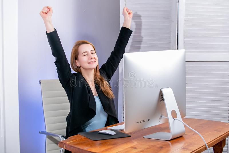 愉快的年轻成功的女实业家画象在办公室庆祝某事与胳膊 情感摆在正随风飘飞的雪木头的时装模特儿 大事,促进 库存图片