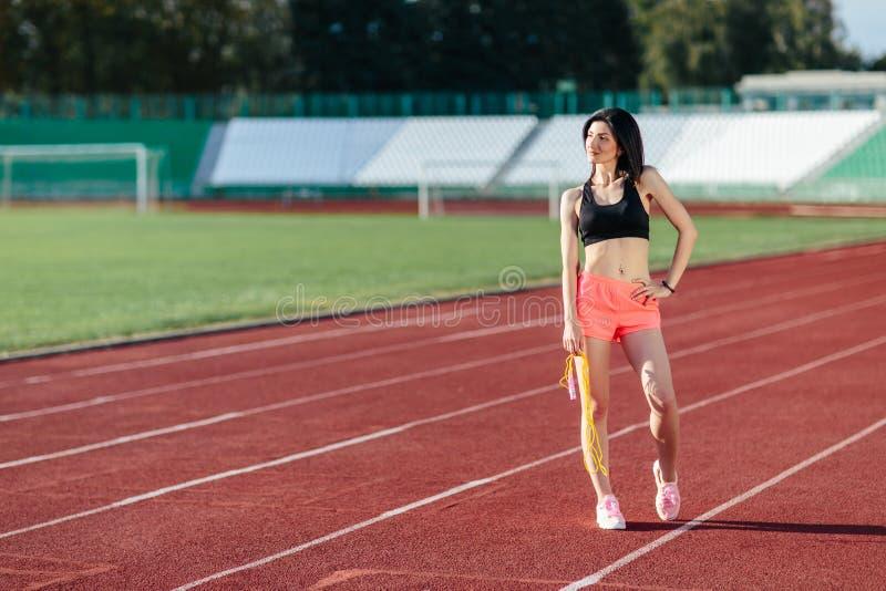 愉快的年轻摆在与在体育场instagram样式的黄色跳绳的运动服的体育深色的妇女 健康活跃 免版税库存照片