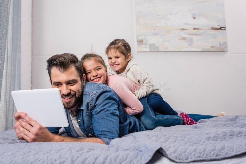 愉快的年轻放松在床上的父亲和女儿 库存照片
