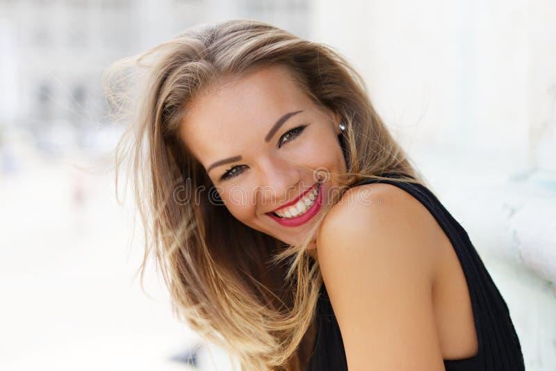 愉快的年轻无忧无虑的妇女微笑的室外画象 免版税图库摄影