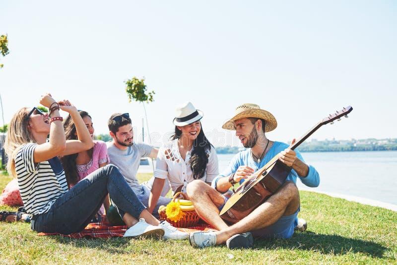 愉快的年轻朋友有野餐在公园 他们是全部愉快的,获得乐趣,微笑和弹吉他 库存照片