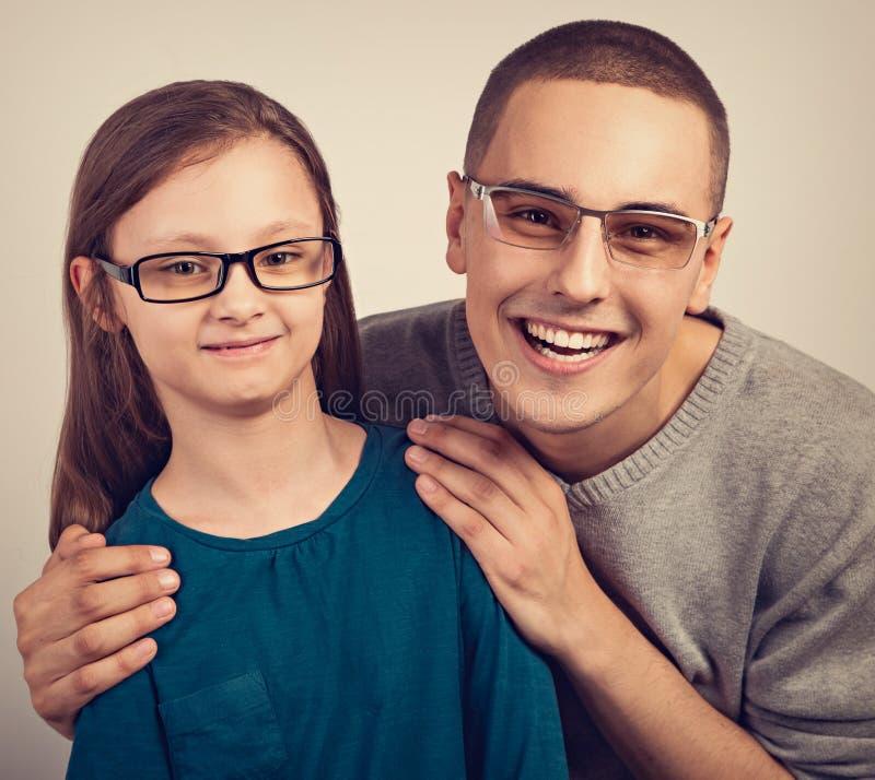 愉快的年轻正面父亲和lauging的孩子在拥抱在空的拷贝空间背景的时尚玻璃 r 免版税库存图片
