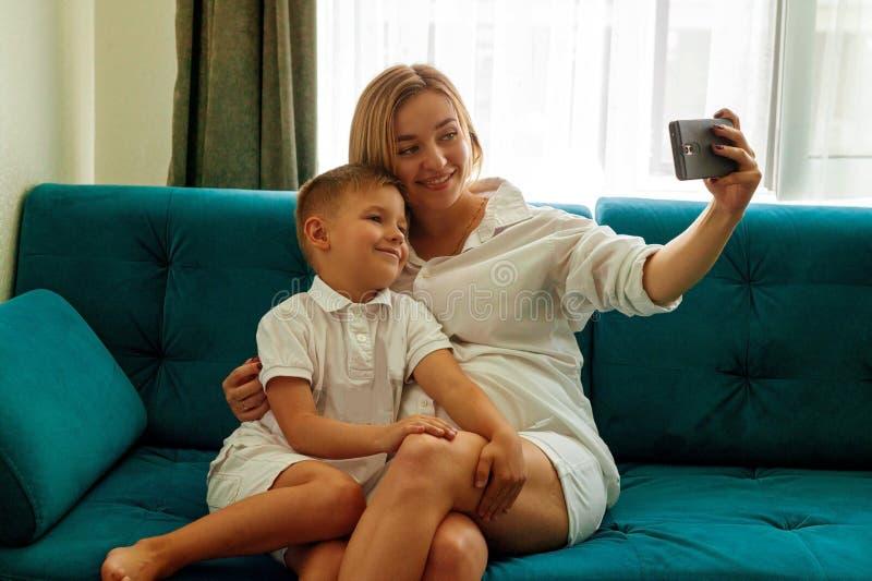 愉快的年轻母亲做与她的儿子的selfie照片 图库摄影